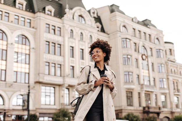 Mooie jonge, gelukkige brunette vrouw in zwarte jurk en trendy beige trenchcoat glimlacht en houdt een koffiekopje buiten