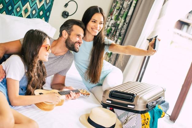 Mooie jonge gelukkige familie selfie foto maken in de slaapkamer en samen plezier