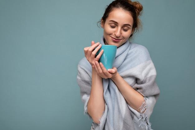Mooie jonge gelukkige glimlachende donkerbruine vrouw die warme blauwe geïsoleerde sjaal draagt