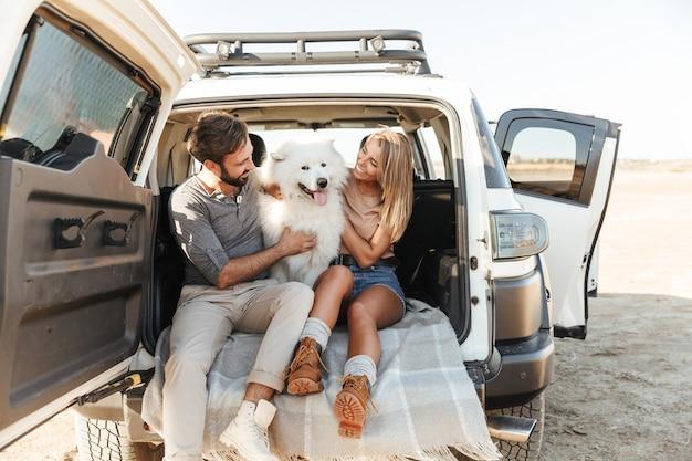 Mooie jonge gelukkige paar zittend in de achterkant van hun auto op het strand, spelen met hond