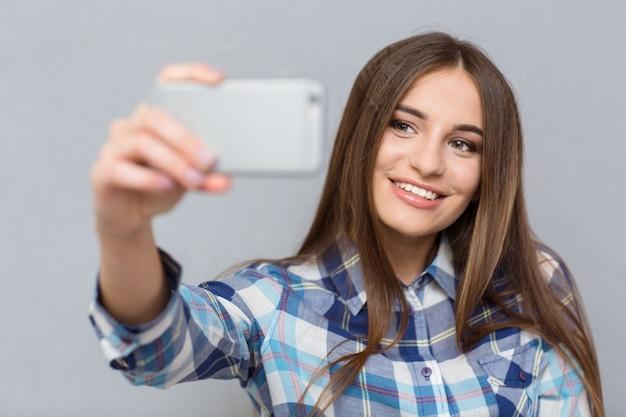Mooie jonge gelukkige vrolijke vrouw in geruit hemd glimlachend en zichzelf neerschietend