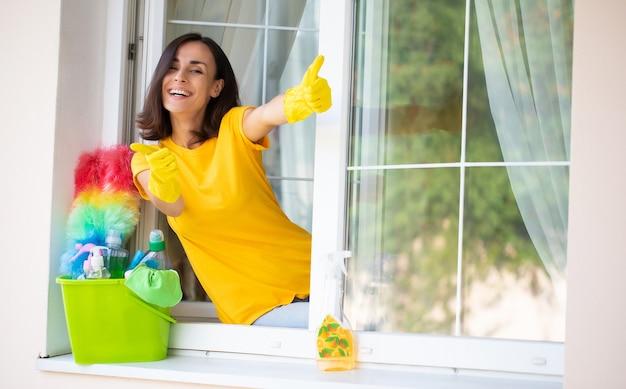 Mooie jonge gelukkige vrouw gebruikt een stofdoek en een spray tijdens het schoonmaken van een raam in het huis