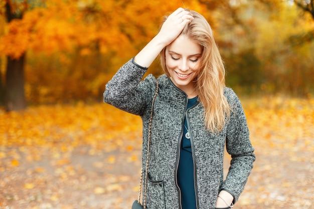 Mooie jonge gelukkige vrouw in modieuze herfstkleren wandelen in een park met gele bladeren