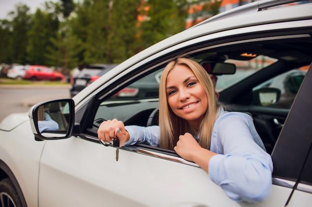 Mooie jonge gelukkige vrouw in nieuwe auto met sleutels - in openlucht