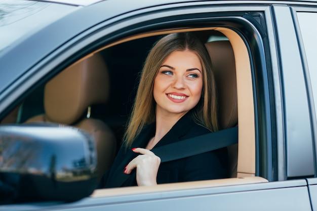 Mooie jonge gelukkige vrouw maakt een veiligheidsgordel in de auto vast