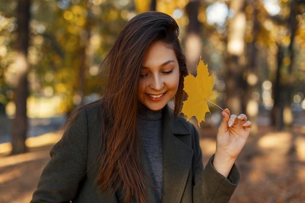 Mooie jonge gelukkige vrouw met een glimlach met een gele herfstblad wandelingen in het park op een zonnige dag