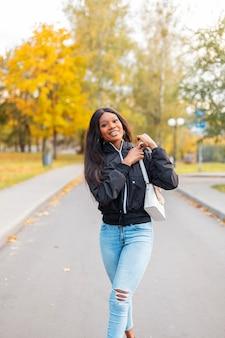 Mooie jonge gelukkige zwarte vrouw in een modieus casual jasje en spijkerbroek met een handtas loopt in het park met gekleurd geel herfstgebladerte