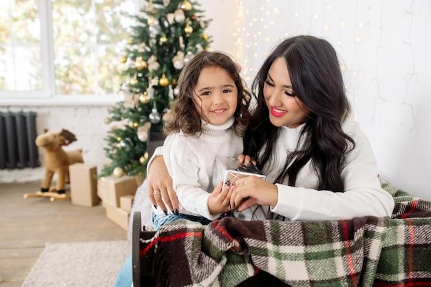 Mooie jonge gemengd ras familie: moeder en dochtertje klaar voor kerst en opening presenteert in de buurt van de kerstboom