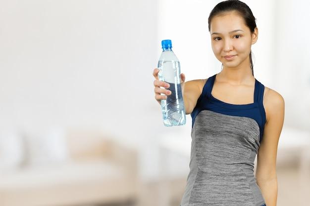 Mooie jonge geschiktheidsvrouw die met perfecte lichaamsvorm zoet water drinkt