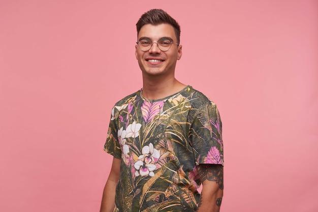 Mooie jonge getatoeëerde man met charmante glimlach poseren, gelukkig kijken, bril en gebloemde t-shirt dragen