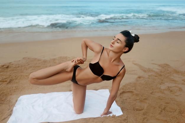 Mooie jonge geweldige mooie fitness vrouw buiten op het strand maken yoga sport oefening. actieve levensstijl. gezond en yogaconcept.