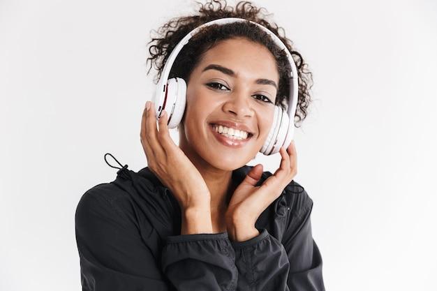 Mooie jonge geweldige sport fitness afrikaanse vrouw luisteren muziek in koptelefoon geïsoleerd over witte muur.
