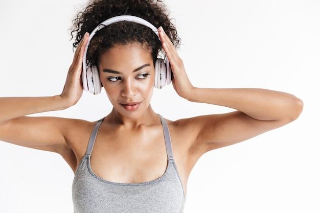 Mooie jonge geweldige sport fitness afrikaanse vrouw poseren geïsoleerd over witte muur luisteren muziek met koptelefoon.