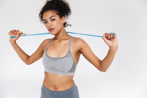 Mooie jonge geweldige sport fitness afrikaanse vrouw poseren geïsoleerd over witte muur met springtouw.