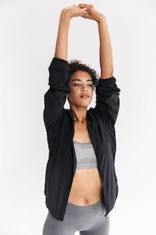 Mooie jonge geweldige sterkere sport fitness afrikaanse vrouw maken oefeningen geïsoleerd over witte muur muur.
