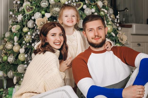 Mooie jonge gezin zit naast een mooi versierde kerstboom