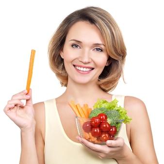 Mooie jonge gezonde vrouw met een bord groenten - geïsoleerd op wit.
