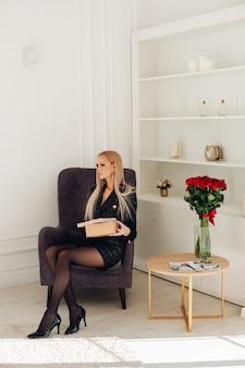 Mooie jonge glamour meisje vrouwelijke mannequin zittend op fauteuil poseren in gezellig interieur met rozen boeket. hoge kwaliteit foto