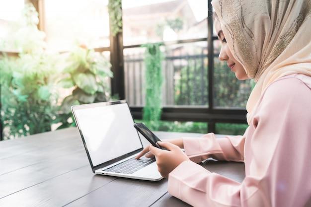 Mooie jonge glimlachende aziatische moslimvrouw die aan telefoonzitting in woonkamer thuis werken