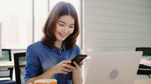 Mooie jonge glimlachende aziatische vrouw die aan laptop werkt terwijl het genieten van van het gebruiken van smartphone op kantoor.