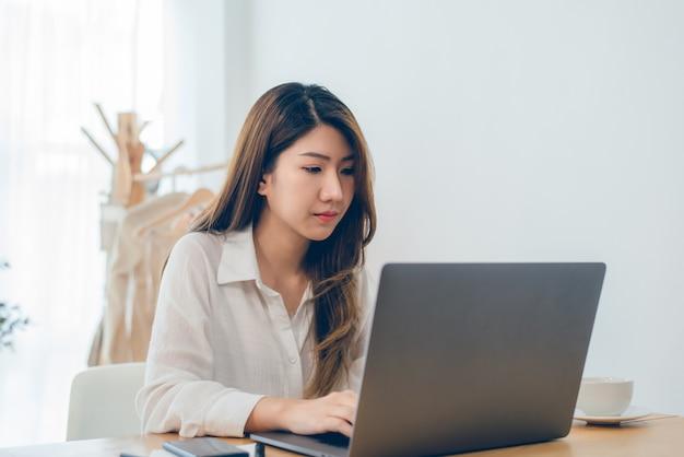 Mooie jonge glimlachende aziatische vrouw die aan laptop werkt terwijl thuis in de ruimte van het bureauwerk