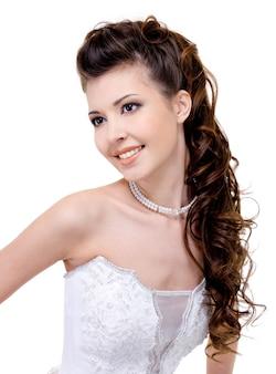 Mooie jonge glimlachende bruid met moderne lang krullende haren van het huwelijkskapsel