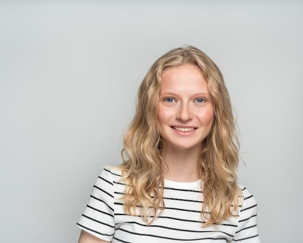 Mooie jonge glimlachende slimme blonde vrouw zonder make-up op witte muur. vrij wijfje met krullend haar in wit t-shirt