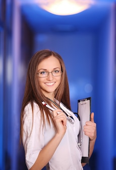 Mooie jonge glimlachende verpleegster in het ziekenhuis gang