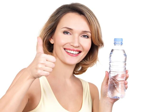 Mooie jonge glimlachende vrouw met een fles water op wit.