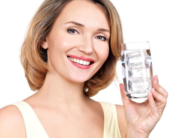 Mooie jonge glimlachende vrouw met een glas water op een witte muur