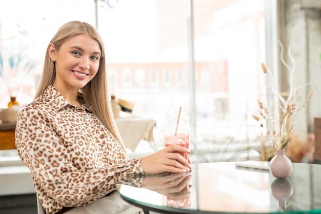 Mooie jonge glimlachende vrouw met lang blong haar met aardbeicocktail zittend aan tafel in café