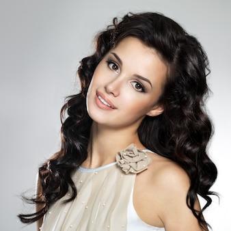 Mooie jonge glimlachende vrouw met lang bruin haar.