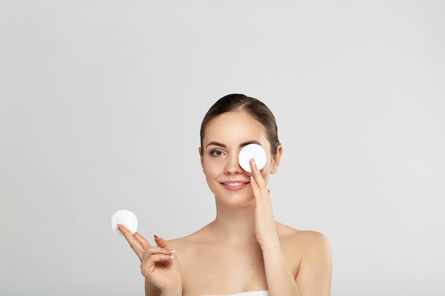 Mooie jonge glimlachende vrouw met schone katoenen stootkussens. gezichtsbehandeling . cosmetologie, schoonheid en spa. schoonheid huidverzorging famale gezicht. expressieve gezichtsuitdrukkingen.