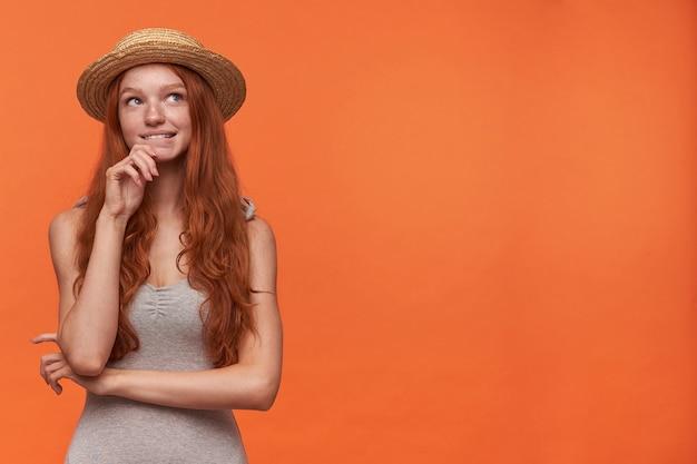 Mooie jonge golvende langharige foxy vrouw in grijs shirt en strooien hoed met haar kin, opzij kijkend met dromerig gezicht en bijten onderlip, geïsoleerd op oranje achtergrond