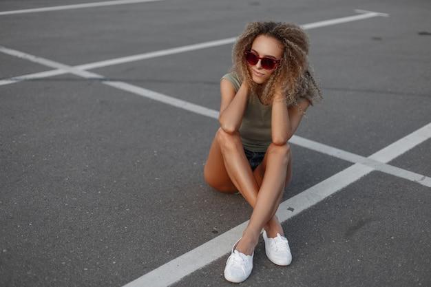 Mooie jonge grappige krullende vrouw met zonnebril in denim shorts en witte sneakers zittend op de weg op het asfalt