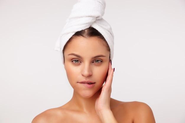Mooie jonge groenogige brunette vrouw met palm op zijn wang en onderlip bijten terwijl flirterige camera kijken, poseren op witte achtergrond met handdoek op haar hoofd
