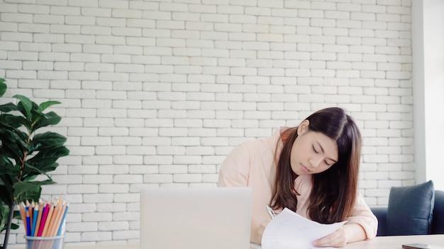 Mooie jonge het glimlachen aziatische vrouwen werkende laptop op bureau in woonkamer thuis.
