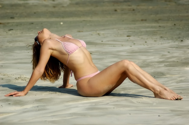 Mooie jonge hete meid in een roze badpak zit op een zandstrand en geniet van de warme zomerzon tijdens een vakantie op zee. sensueel jong vrouwenconcept