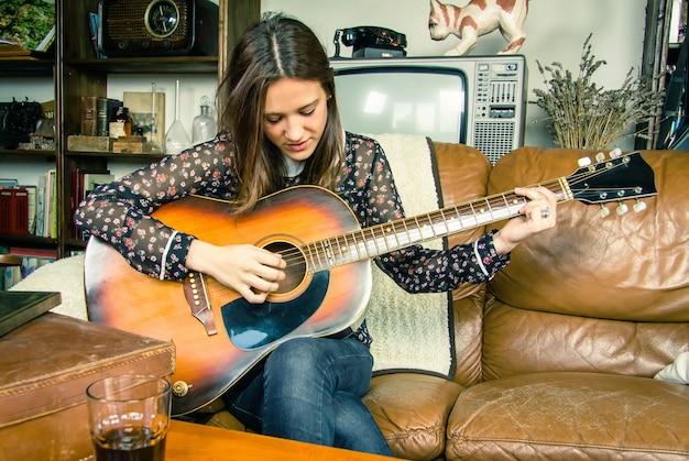 Mooie jonge hipster meisje akoestische gitaar spelen zittend in een bank thuis. retro vintage kleuren editie