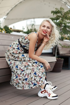 Mooie jonge hipster meisje in modieuze jurk met patronen en stijlvolle schoenen, zittend op een bankje en genieten van het moment