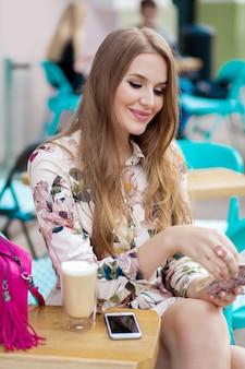 Mooie jonge hipster stijlvolle vrouw zitten in café