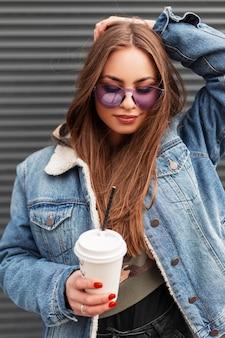 Mooie jonge hipster vrouw in stijlvolle glamoureuze paarse bril in trendy blauw spijkerjasje met koffie rechtzetten haar en glimlachen in de buurt van grijze metalen muur. amerikaans meisje mannequin poseren in de stad.