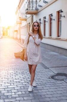 Mooie jonge hipster vrouw in stijlvolle zonnebril in een stijlvolle roze zomerjurk in witte sneakers met een stijlvolle lederen tas poseren op een vintage straat in de stad op een zonnige dag. stijlvol blond meisje