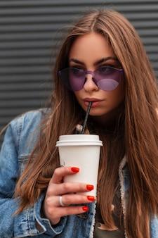 Mooie jonge hipster vrouw in vintage violet bril in modieuze kleding drinkt zoete drank met rietje. modern meisjesmodel in blauw spijkerjasje geniet van koffie in de buurt van de grijze metalen muur.