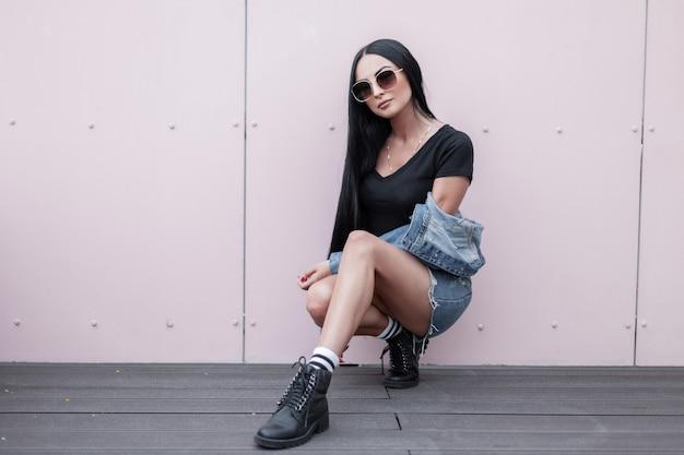 Mooie jonge hipster vrouw in zonnebril in een modieuze blauwe denim kleding in stijlvolle lederen zwarte herfst laarzen zittend in de buurt van een muur op straat. sexy stedelijke meisje ontspant buitenshuis. straatmode.