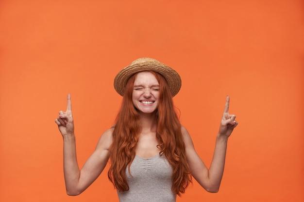 Mooie jonge hoopvolle roodharige langharige vrouw poseren binnen met gesloten ogen, naar boven met duimen opdagen en positief glimlachen, geïsoleerd op oranje achtergrond