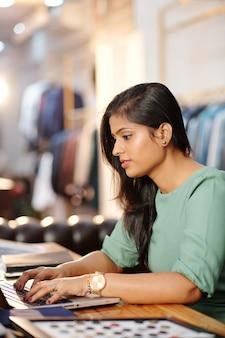 Mooie jonge indiase ateliereigenaar die op laptop werkt, stoffen bestelt en e-mails van klanten beantwoordt