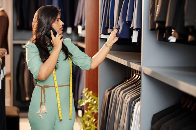 Mooie jonge indiase kleermaker die telefonisch met de klant praat bij het controleren van afgewerkte, op maat gemaakte jassen die aan het spoor hangen