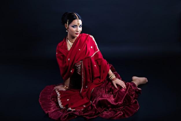 Mooie jonge indiase vrouw in traditionele kleding en indiase accessoires