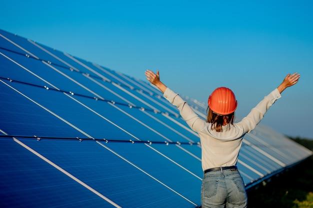 Mooie jonge ingenieur permanent in de buurt van zonnepanelen buitenshuis, green energy concept.